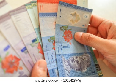 hand holding malaysia currency-ringgit.counting money.There is one,ten,fifty,one hundred notes.