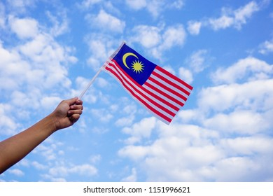 Hand holding a Malaysia flag with sky background