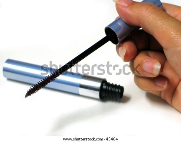 a hand holding a mascara brush