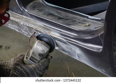 Hand holding matel grinding eguipment for car body repair work.