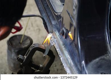 Hand holding matel welding eguipment for car body repair work.