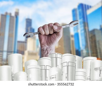 Hand holding mechanic key with architect plans and city background