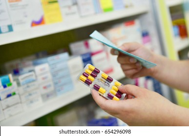 Hand holding medicine capsule pack at the pharmacy drugstore.