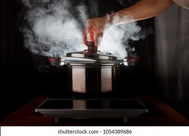 hand holding of metal pot cover with hot steam flowing from inside
