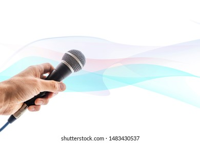 hand holding microphone on abstract background