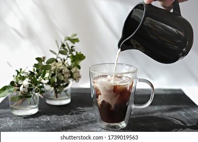Handhaltung Melker und Milch in einen Kaffeekrug gießen. kalter Kaffee mit Eiswürfeln und Blumen auf einem grauen Tisch. Frühstückszeit am Morgen. Relaxkonzept.