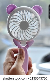 Hand holding mini portable cute electric fan on blurred background.