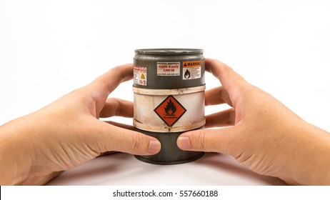 Hand holding miniature of grey color barrel or flammable drum. Concept of dangerous or explosive material. Isolated on white background. Slightly de-focused and close-up shot. Copy space.
