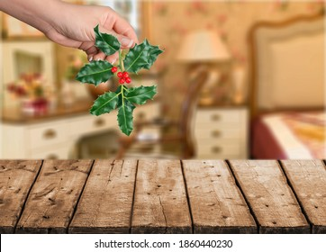 A hand holding mistletoe christmas branch