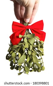 Hand holding mistletoe upside down with red bow on white