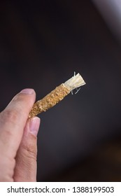 Hand holding miswak or siwak sticks over the black. Great photo for your needs.
