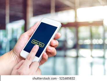 Hand holding mobile  with apply now and empty screen for adding your design at blur hallway offcie building background bokeh light,Mock up for display of logo