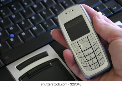 hand holding mobile cell phone with laptop background