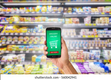 Hand holding mobile with grocery online on screen with blur supermarket background