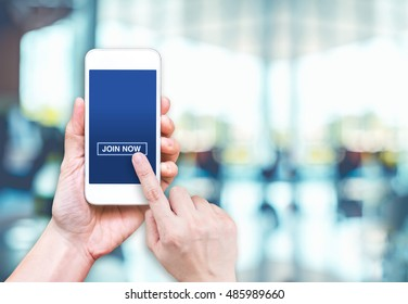 Hand holding mobile  with join now and empty screen for adding your design at blur hallway offcie building background bokeh light,Mock up for display of logo.