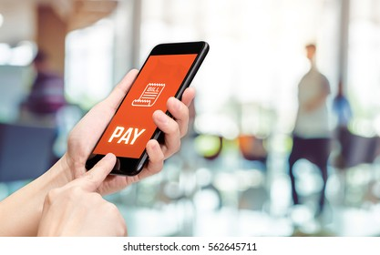 Hand holding mobile with pay word and bill icon feature with blur back office counter background,Digital Lifestyle concept