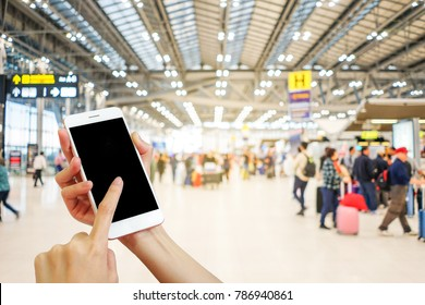 Hand holding mobile phone with airport terminal blurred crowd of Travelling people on the background, Bokeh light, Social network, internet,Traveling concept