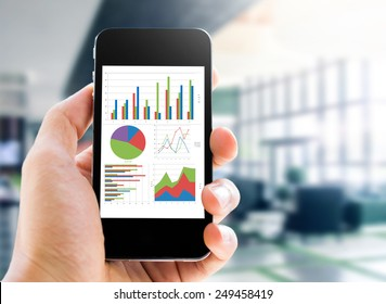 hand holding mobile phone with analyzing graph