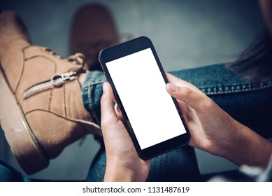 hand holding  mobile phone with blank white screen on thigh with  canvas shoes  tile floor in cafe