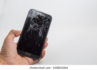 Hand holding mobile phone with broken screen