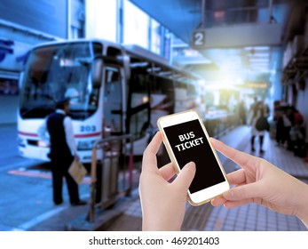 Hand holding mobile phone with E-Ticket word with blur bus terminal  background,Digital Marketing concept; retro color effected