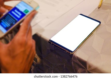 hand holding Mobile phone In the meeting room.and The phone is placed on the table. with blank copy space screen for your advertising text message or promotional content. For Graphic display montage.