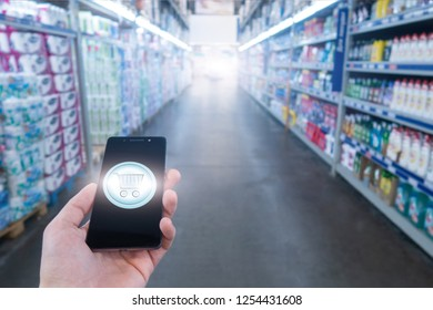 Hand holding mobile phone on Supermarket blur background. Shopping basket on a mobile phone screen.
