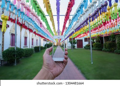 Hand holding mobile phone on festival