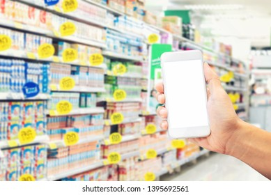 Hand holding mobile phone on shopping center blur in background,Online shopping concept.