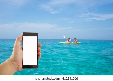 hand holding mobile phone on lady paddling the kayak blur background