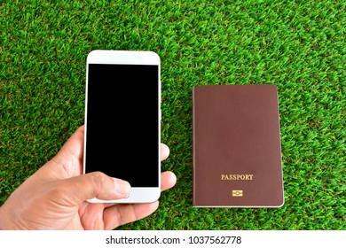 Hand holding mobile phone , pass port on green grass. Can used for business and traveling concepts.