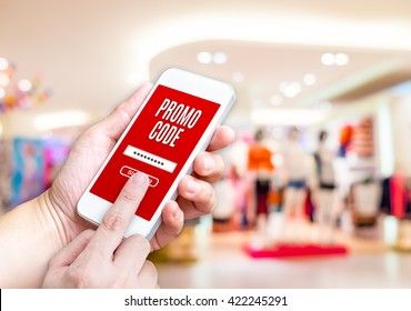 Hand holding mobile phone with promo code word with blurred store background with bokeh light ,internet marketing concept,E-commerce