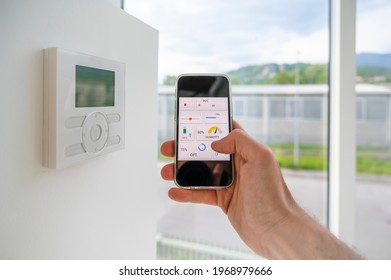Hand holding a mobile phone showing an home automation app to manage online technology in a modern loft.