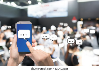 Hand holding mobile phone showing chat message when Live via social network over Abstract blurred photo of conference hall or seminar room with attendee background, business technology concept