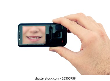 Hand holding mobile phone with smile on display