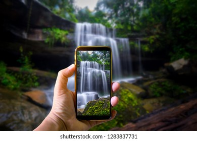 Hand holding mobile phone and take a photo fresh waterfall on blurred background with sunlight.