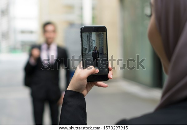 Hand holding mobile phone and taking photo