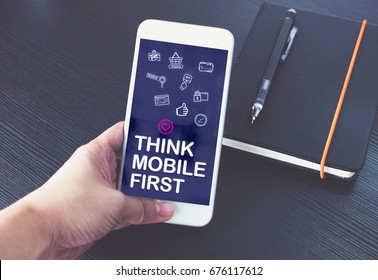 Hand holding mobile phone with Think mobile first word and feature icon over notebook on black wood table background,Digital marketing concept ,office desk
