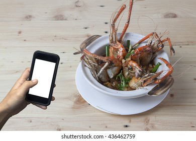 hand holding mobile phone with tiger prawn cooking Chinese style on wooden background