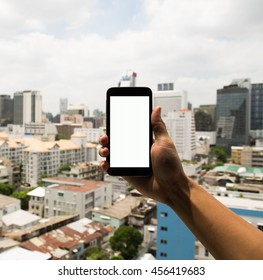 hand holding mobile phone with urban background in Bangkok Thailand