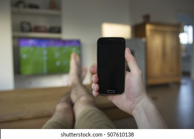 A hand holding a mobile phone which displays a black touch screen. The background is a living room with a TV which displays a soccer match. The person's feet are laying on the wooden table.