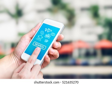 Hand holding mobile with search button with factor of travel icon at blur outdoor resort with beach umbrella background bokeh light,Online booking apps