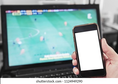 Hand holding mobile smart phone, blank white screen while watching football match