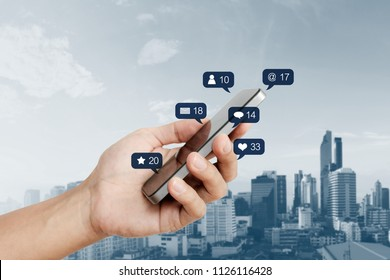 Hand holding mobile smart phone, with social media and social network notification icon