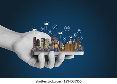 Hand holding mobile smart phone with modern buildings hologram. Smart city, 5g, internet and networking technology concept
