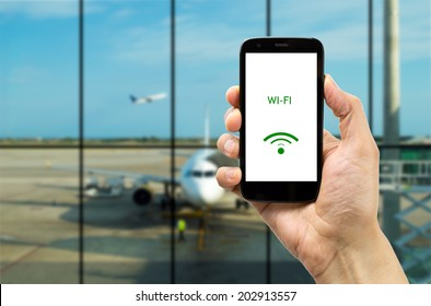 Hand holding mobile smart phone with connect wifi on the airport