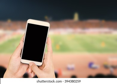 Hand holding mobile smart phone with black screen, blur image of a football field as background.