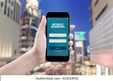 Hand holding mobile smart phone with mobile banking screen on city background