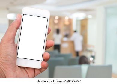 Hand holding mobile smart phone with blank screen in vertical position, blurred people in hospital background - mockup template
