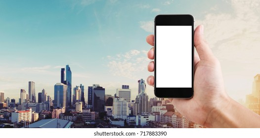Hand holding mobile smart phone blank white screen, panoramic Bangkok city in sunrise